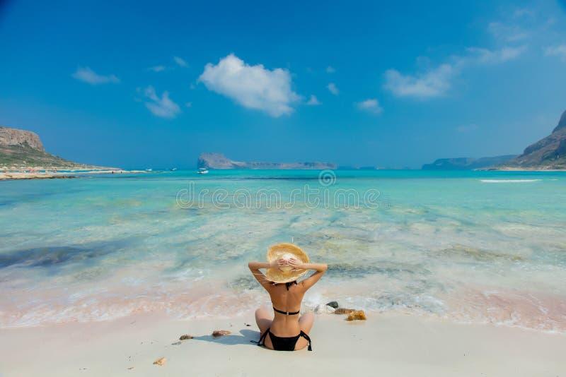 Menina no biquini preto e com o chapéu na praia de Balos foto de stock royalty free