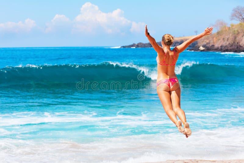 Menina no biquini que salta altamente na praia do mar imagem de stock