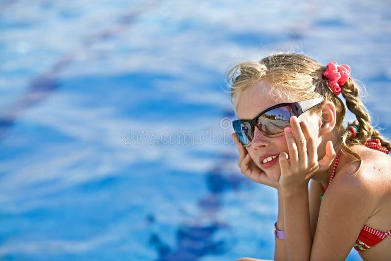 A menina no biquini vermelho, vidros aproxima a piscina. imagens de stock royalty free