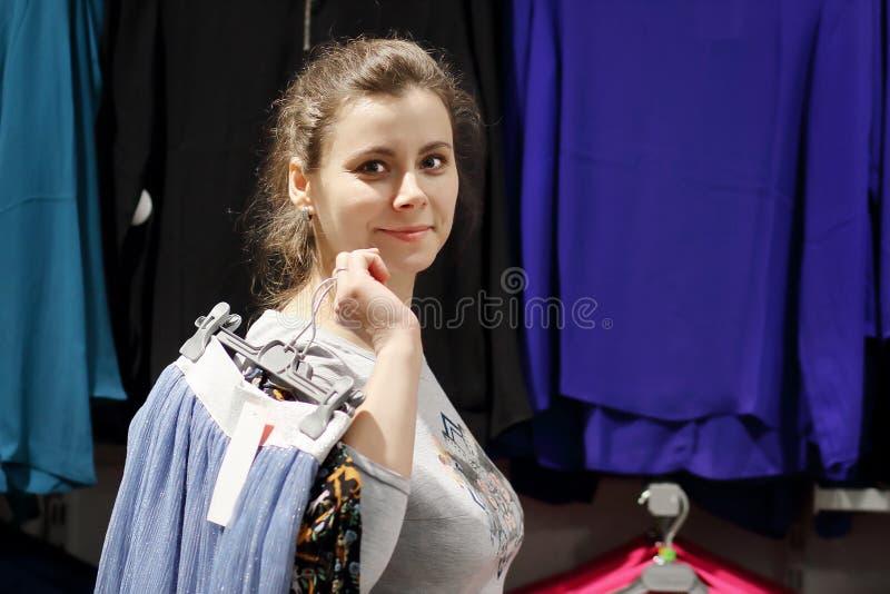 A menina no boutique da forma obteve a roupa e vai ao vestuario Conceito da compra A jovem mulher atrativa escolhe a roupa na loj foto de stock royalty free