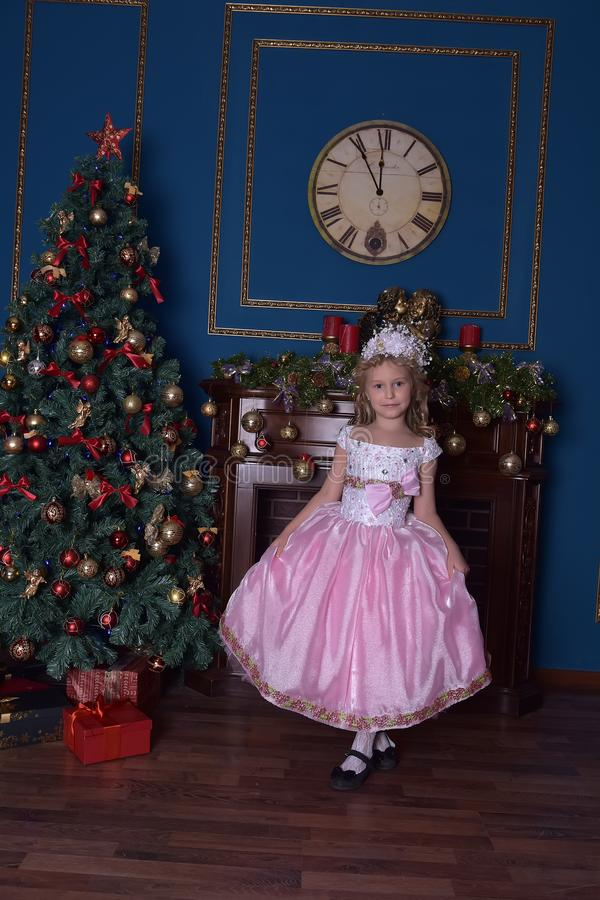 Menina no branco com um vestido cor-de-rosa no Natal fotografia de stock