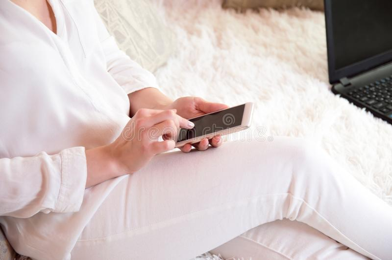 A menina no branco guarda o telefone em suas mãos Leia a notícia no telefone Um homem com um telefone em suas mãos fotografia de stock