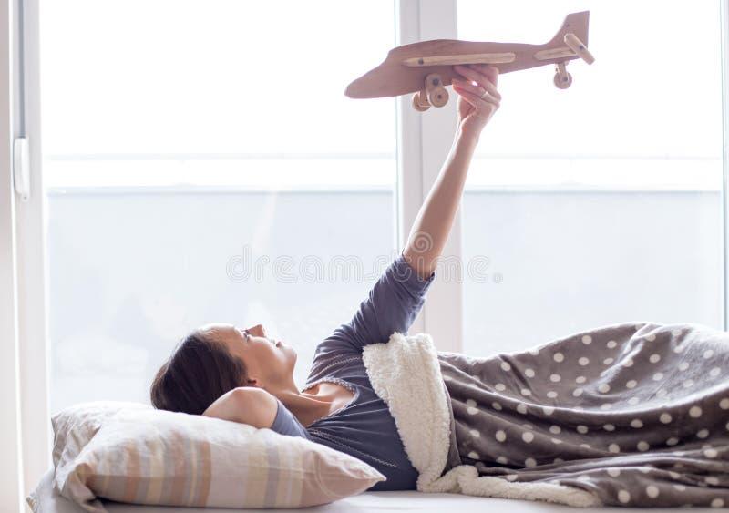 Menina no brinquedo e em sonhar acordado do avi?o da terra arrendada da cama fotografia de stock royalty free