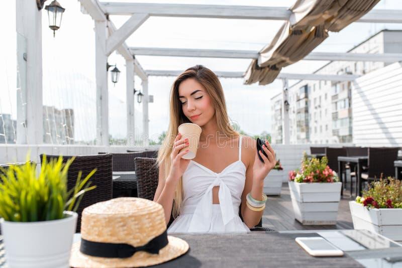 A menina no café Aspira e aprecia o café, inala o aroma obtém o prazer do cheiro do chá Verão de relaxamento fotos de stock royalty free