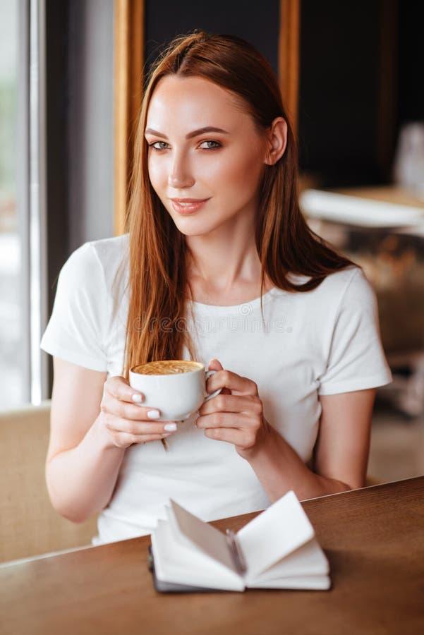 Menina no café com capuccino imagens de stock