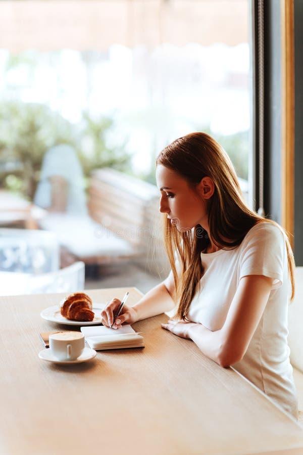Menina no café com capuccino fotografia de stock