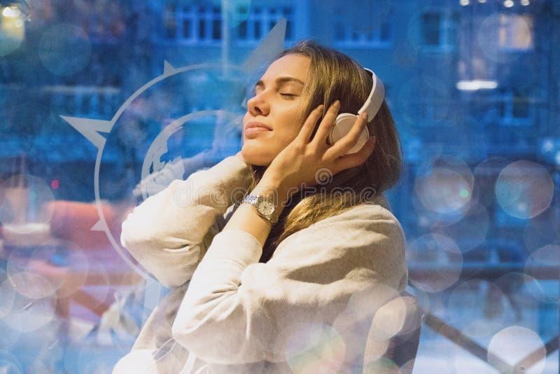 A menina no café que senta-se nos fones de ouvido e aprecia o mus fotos de stock royalty free