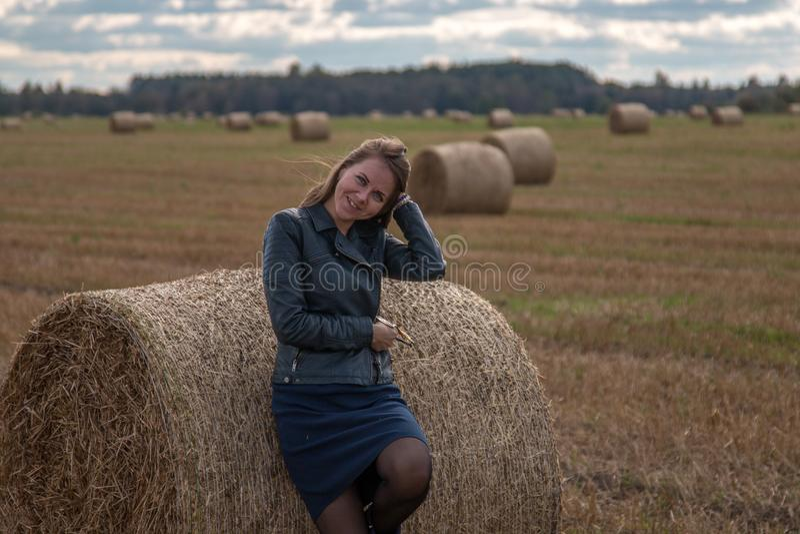 Menina no campo ao lado da pilha imagem de stock royalty free