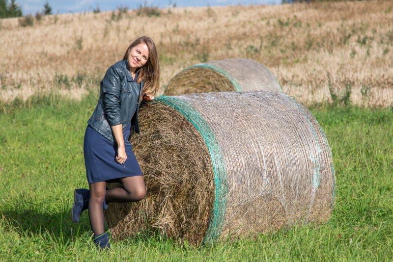Menina no campo ao lado da pilha fotografia de stock