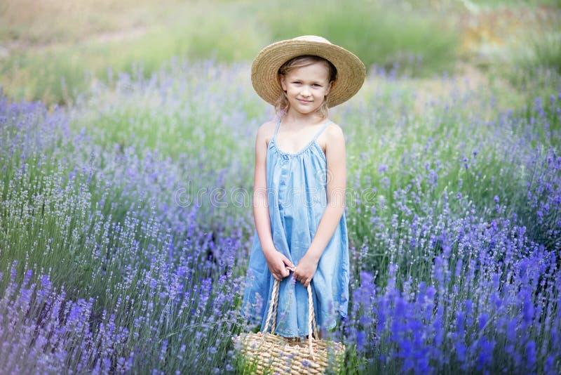 Menina no campo da alfazema Ca?oa a fantasia Menina de sorriso que aspira flores no campo roxo da alfazema do verão imagem de stock