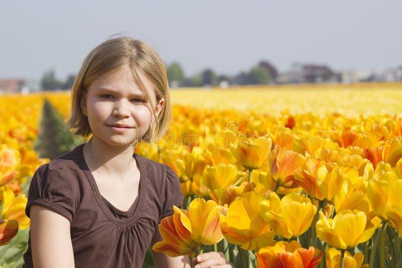 Menina no campo dos tulips fotografia de stock royalty free