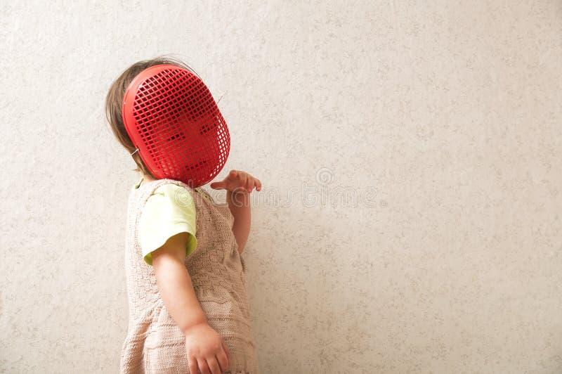 Menina no capacete da cerca Jogando o papel astuto na máscara de cerco Sorriso e criança feliz que jogam o jogo lote do espaço pa fotografia de stock