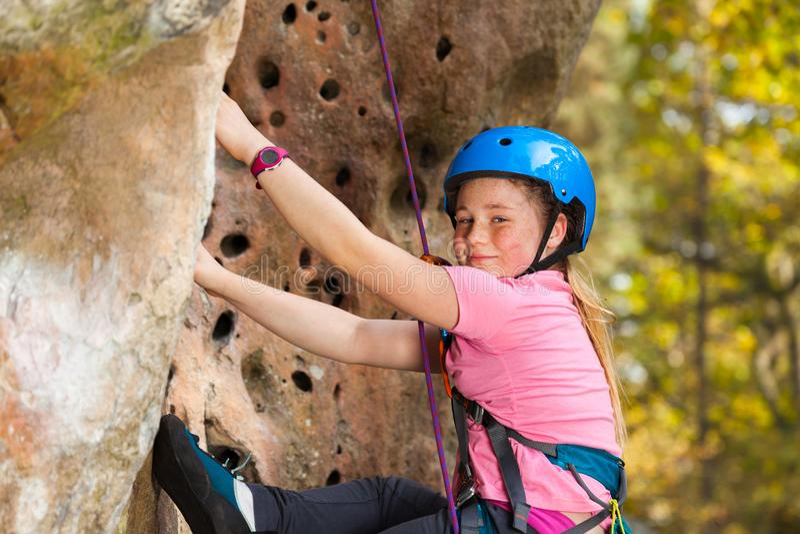 Menina no capacete de segurança que escala na rota da rocha foto de stock