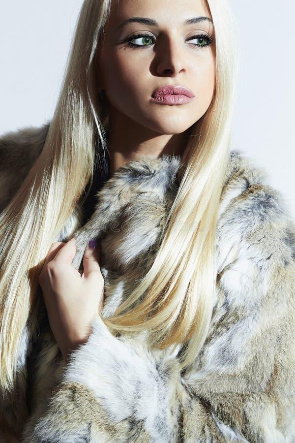 Menina no casaco de pele Mulher luxuosa bonita do inverno Menina loura na pele do coelho imagem de stock
