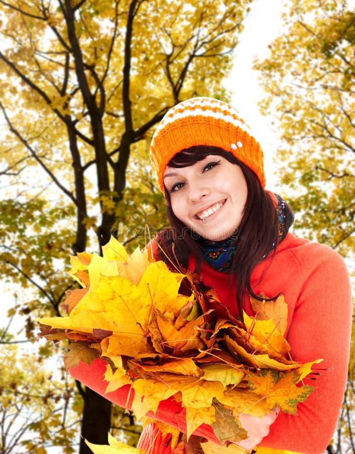 Menina no chapéu alaranjado do outono, grupo da folha perto da árvore.