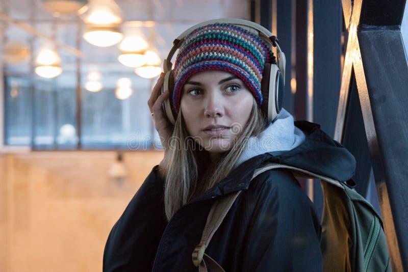 A menina no chapéu colorido e em fones de ouvido maciços marrons está na passagem subterrânea fotos de stock royalty free