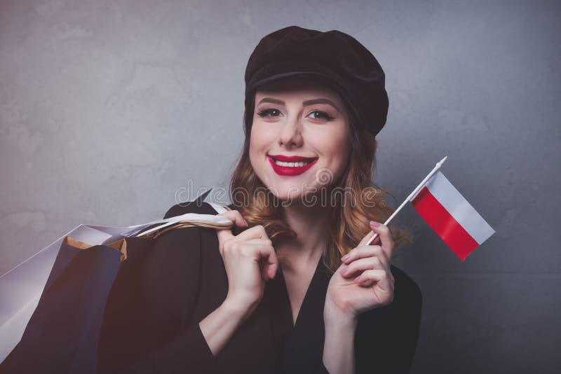 Menina no chapéu com sacos de compras e bandeira do Polônia fotografia de stock royalty free