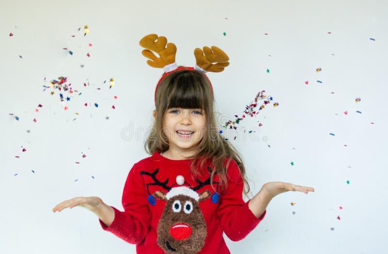 Menina no chapéu de Rudolf que espera um Natal no fundo branco imagem de stock