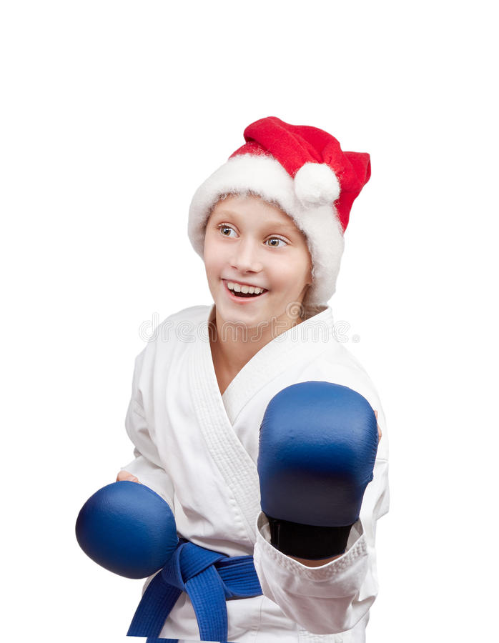 Menina no chapéu de Santa Claus que está na cremalheira do karaté fotografia de stock