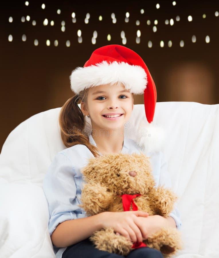 Menina no chapéu de Santa com o urso de peluche no Natal foto de stock