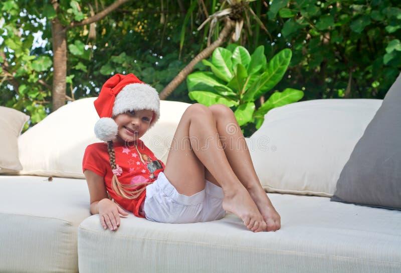 Menina no chapéu de Santa entre árvores tropicais imagens de stock royalty free