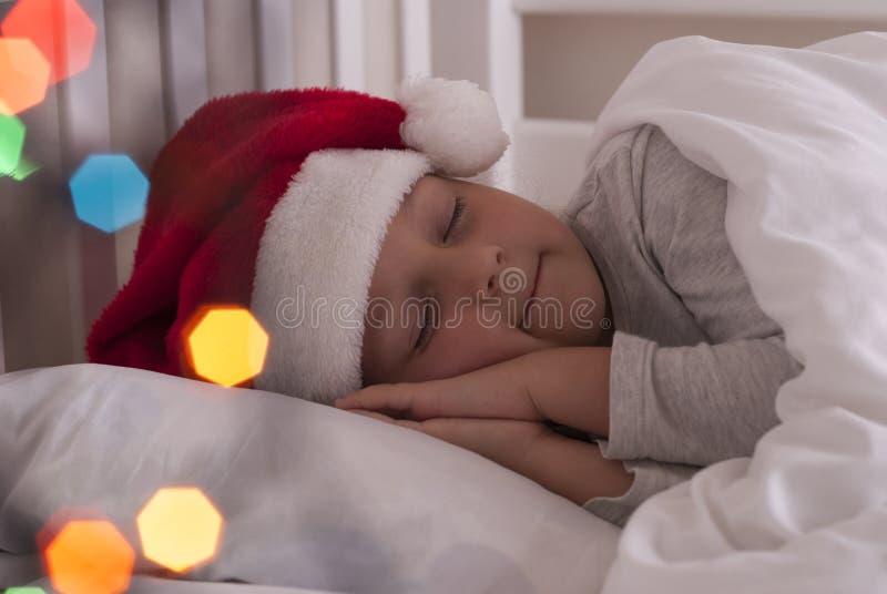 Menina no chapéu de Santa na cama foto de stock royalty free
