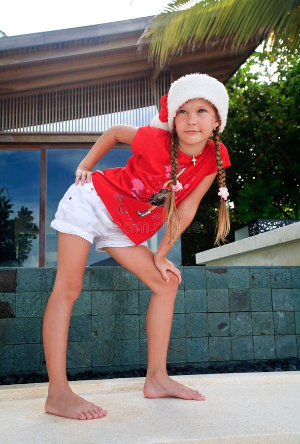 Menina no chapéu de Santa nos tropics imagem de stock royalty free