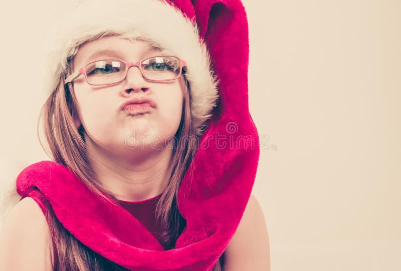 Menina no chapéu de Santa que faz a cara parva imagem de stock royalty free