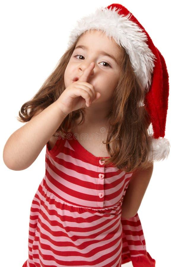 Menina no chapéu de Santa que gesticula a paz e o quiet fotos de stock