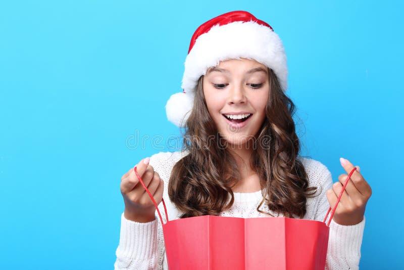Menina no chapéu de Santa que guarda o saco de compras imagem de stock
