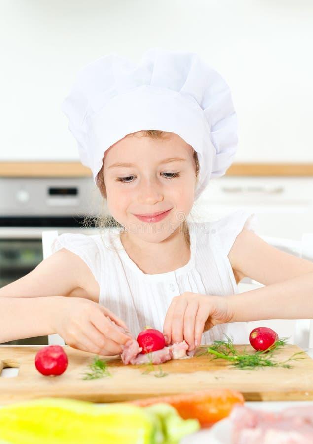 Menina no chapéu do cozinheiro chefe fotos de stock