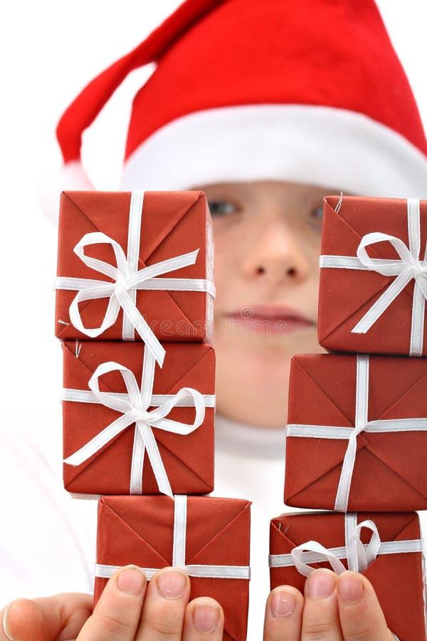 Menina no chapéu do ed de Santa com os seis presentes isolados imagens de stock royalty free