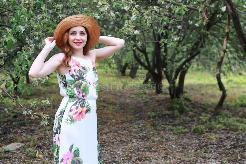Menina no chapéu do vestido e de palha no parque fotos de stock royalty free