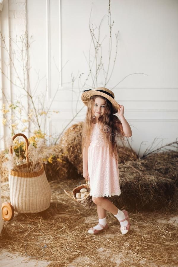 Menina no chapéu do vestido e do feno que mantém a cesta com pouco pintainho imagem de stock