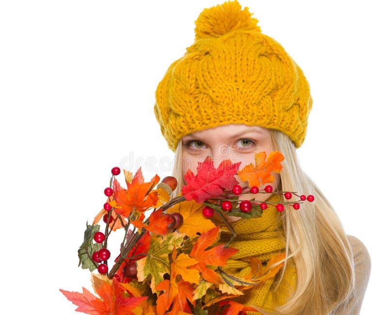 Menina no chapéu e no lenço que escondem atrás do ramalhete do outono fotografia de stock royalty free