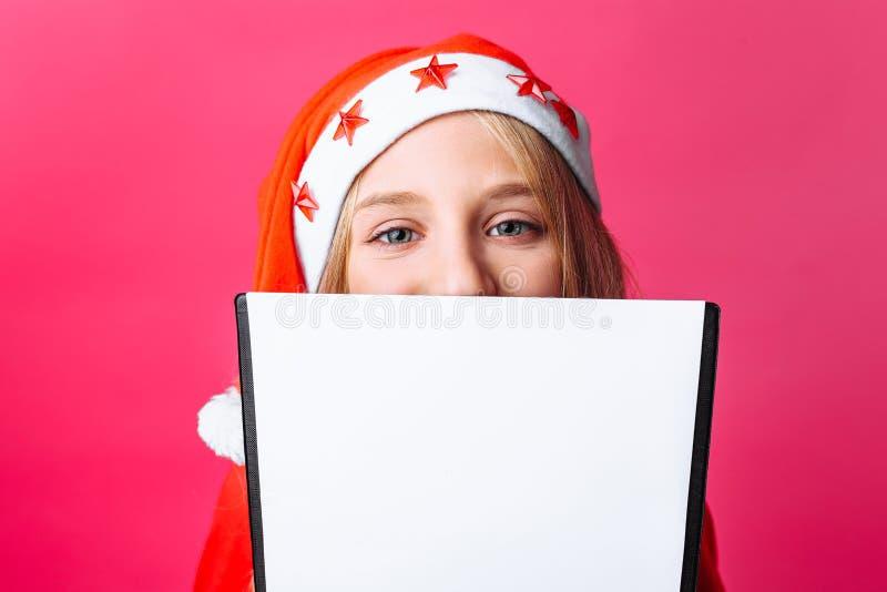 Menina no chapéu e no ouropel de Santa no pescoço, um adolescente que guarda um t foto de stock