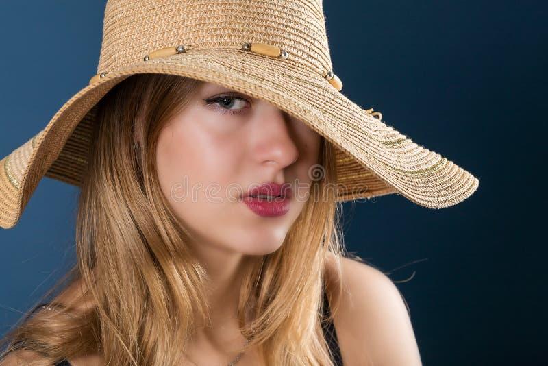 A menina no chapéu grande do sol e nos bordos vermelhos fotos de stock royalty free
