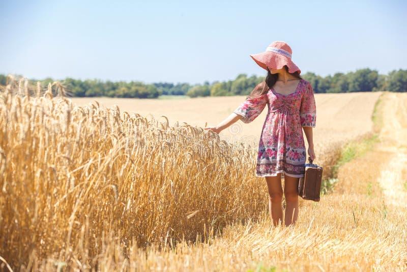Menina no chapéu no campo de trigo imagens de stock