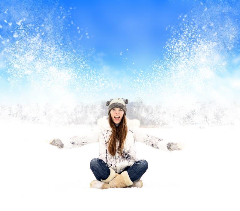 Menina no chapéu que senta-se na neve foto de stock royalty free
