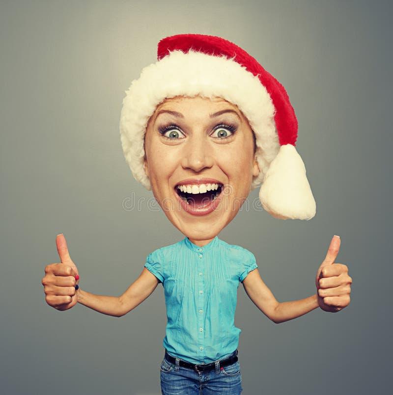 Menina no chapéu vermelho que mostra os polegares acima fotos de stock