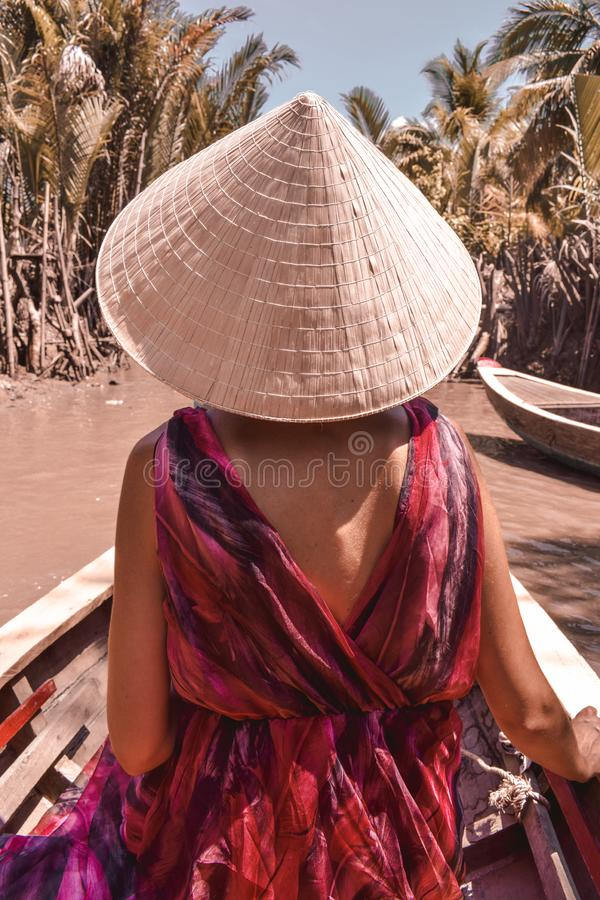 Menina no chapéu vietnamiano cilíndrico típico que flutua em um barco através dos manguezais no delta de Mekong imagens de stock