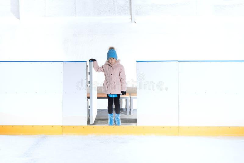 A menina no chap?u azul e no revestimento cor-de-rosa est? indo para a patinagem no gelo imagens de stock royalty free