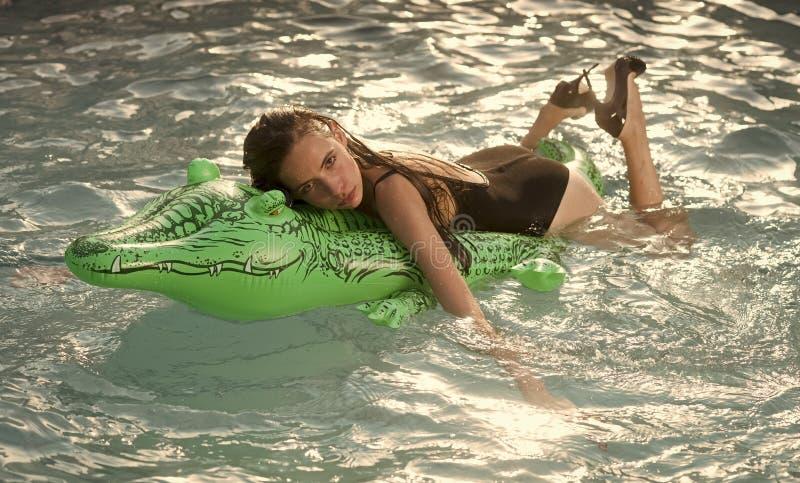 Menina no crocodilo inflável do colchão na associação fotos de stock royalty free