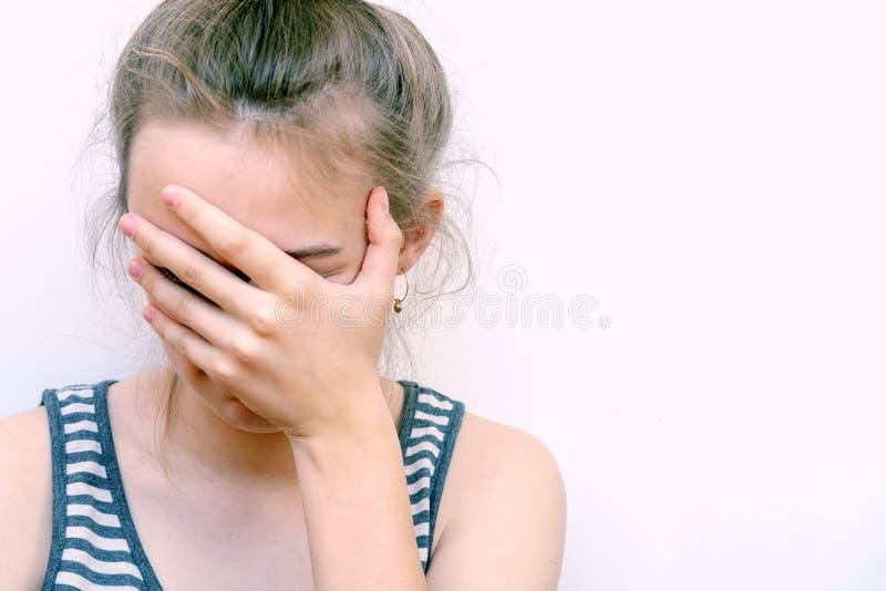 A menina no desespero cobre sua cara com a mão Retrato for?ado da f?mea da dor da dor de cabe?a da mulher em casa fotografia de stock