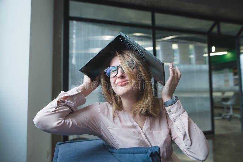 A menina no desespero fez sobre a cabeça um telhado de um portátil A menina triste falhou e gritos deadline imagens de stock