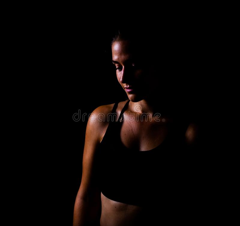 Menina no desgaste do esporte que olha abaixo do isolado com o baixo tiro chave do fundo preto fotos de stock