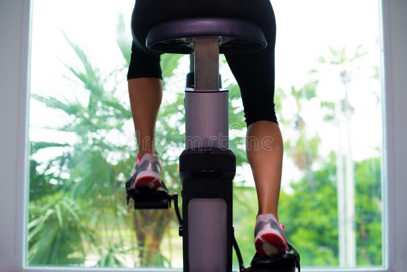 A menina no desgaste preto do esporte trabalha vigorosamente na bicicleta de exercício, vista traseira foto de stock