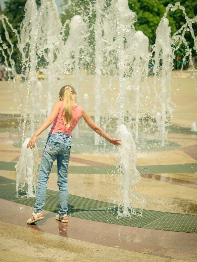 Menina no dia ensolarado que joga com água fresca na fonte da cidade fotografia de stock