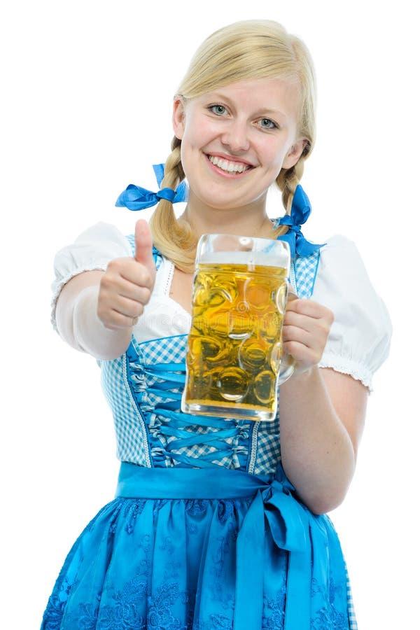 A menina no dirndl de Oktoberfest guarda o caneco de cerveja da cerveja de Oktoberfest fotografia de stock