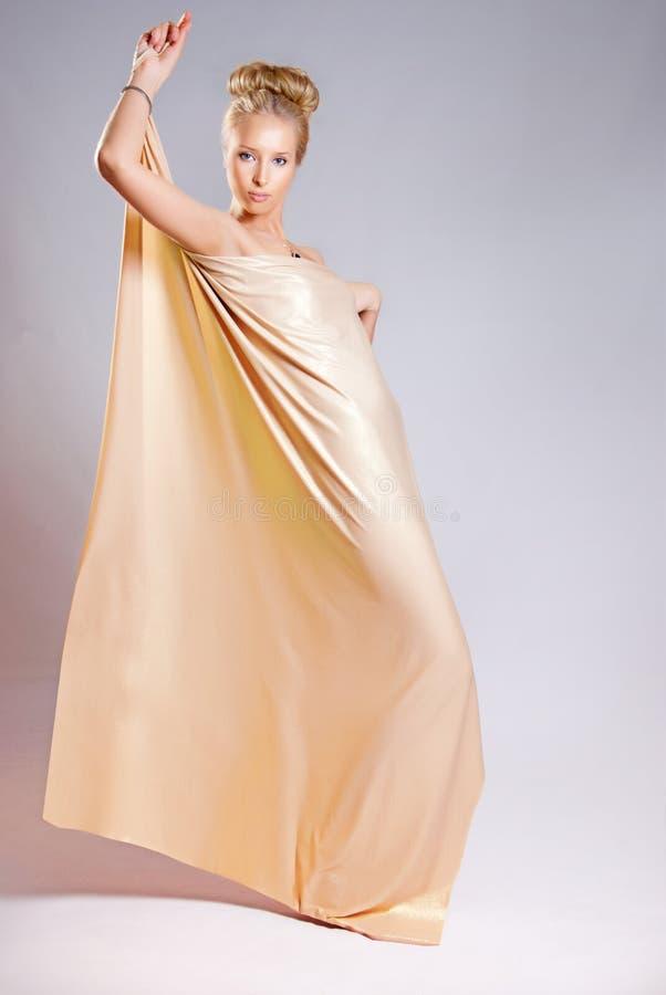 Menina no drapery dourado imagem de stock